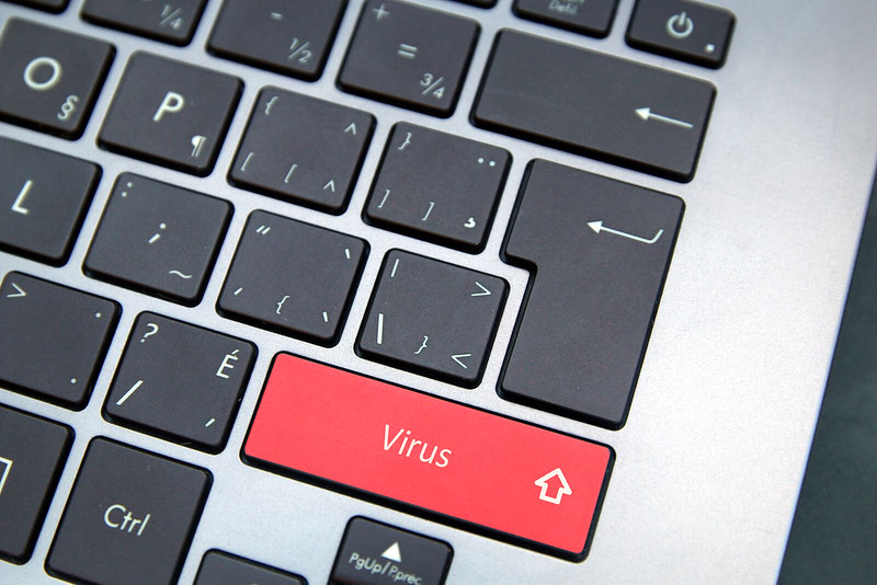 Cyber security virus written on laptop keyboard