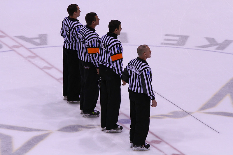 White team represented by four hockey officials on the ice